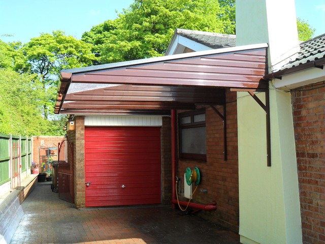 A2z Canopies Brown Cantilever Carport with GRP sheeting, Aluminium facia and Guttering with red garage door behind it