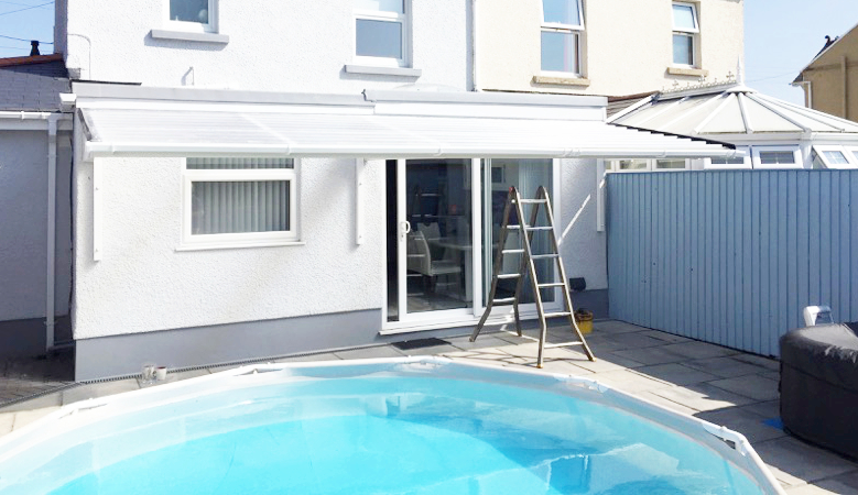 A2z Canopies White Cantilever Patio Canopy with GRP sheeting in front of a swimming pool, Aluminium facia and Guttering
